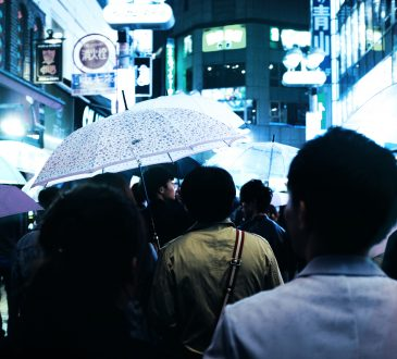 people walking in rain through busy city
