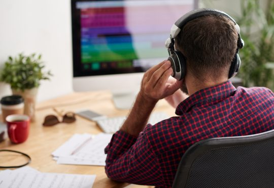 man sitting at desk wearing over-ear headphones