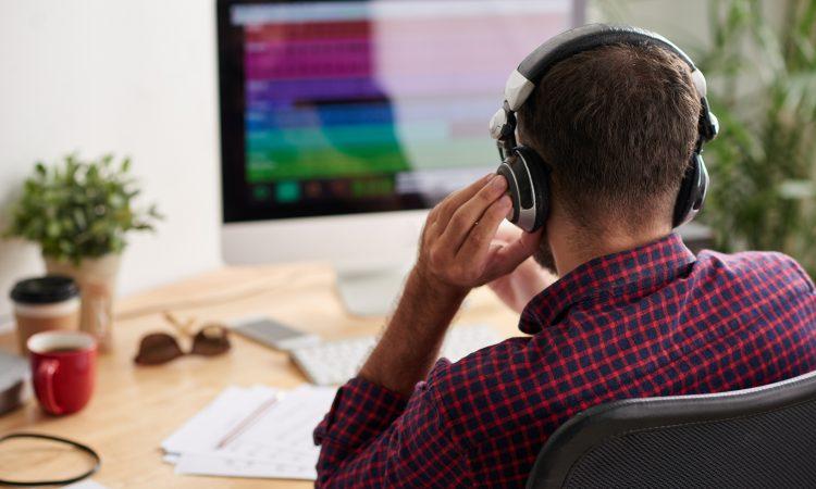 man sitting at desk wearing over-ear headphones