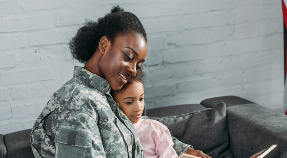 female soldier reading book with daughter