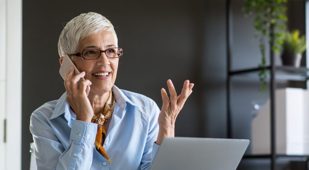 Mature businesswoman talking On the phone in her office.