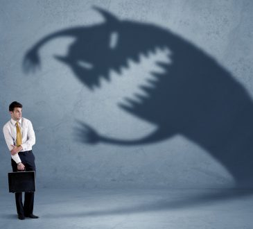 businessman cowering beside shadow of monster
