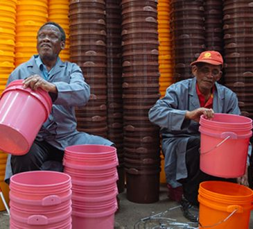 two men stacking buckets