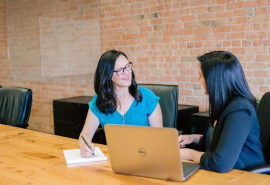 two women sitting at long table talking