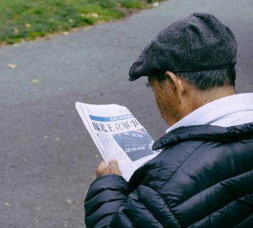 older man reading newspaper on bench outside