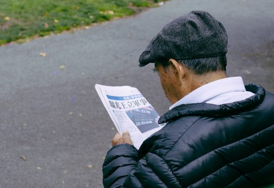 older man reading newspaper on bench outside