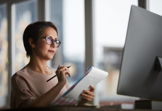 woman taking notes on notepad in front of computer screen