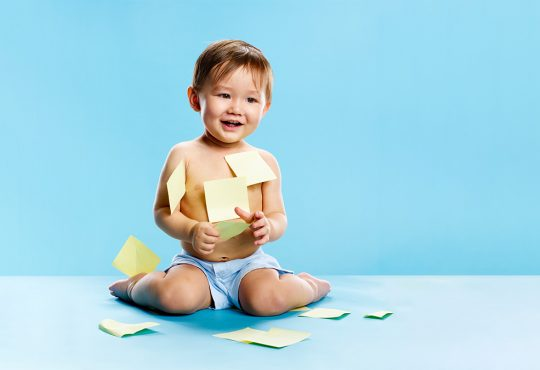 toddler boy playing with sticky notes