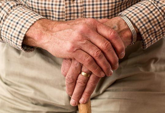 closeup of older man's hands holding cane
