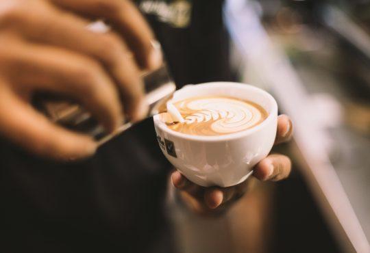 barista pouring latte