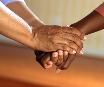 person clasping another person's hands