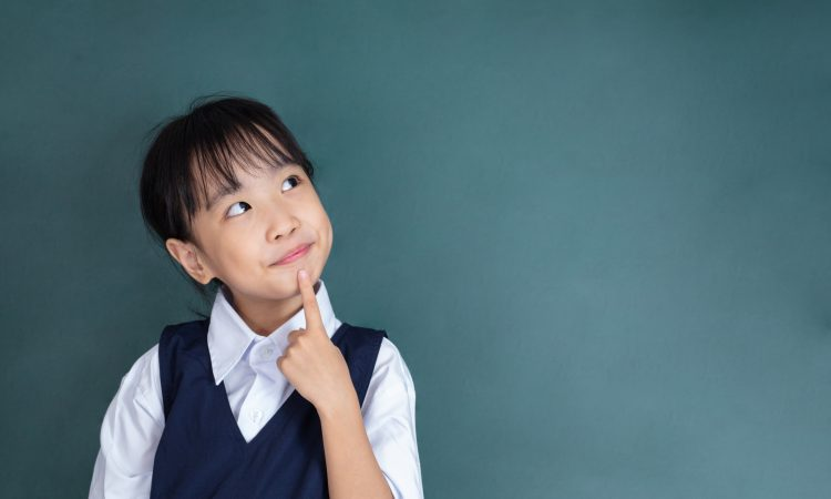 little Girl thinking with finger on chin against green blackboard