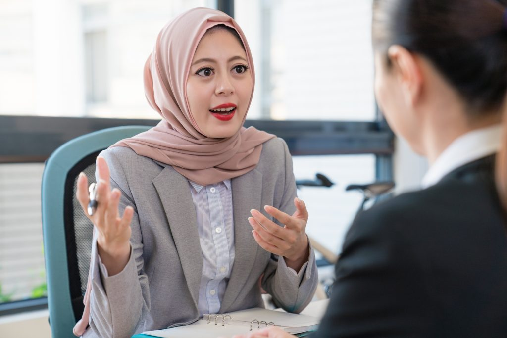 woman wearing hijab talking to other woman in office