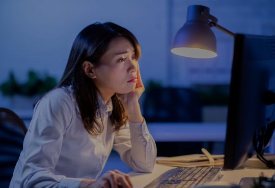 woman working late, looking stressed