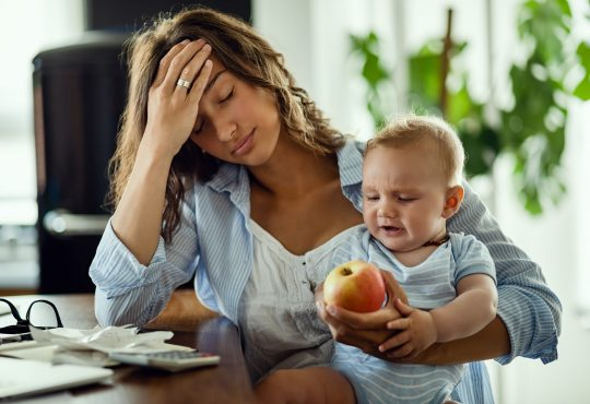 Young mother feeling exhausted while being with her baby and working at home.
