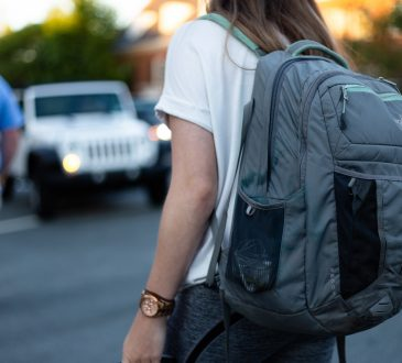 teen girl walking outside wearing backpack