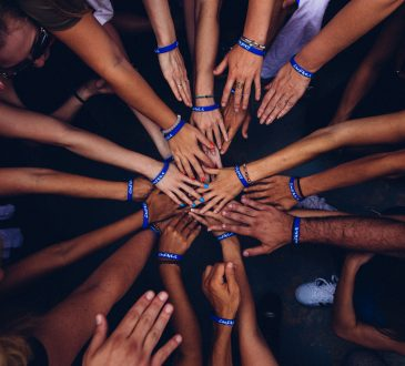 group of people huddling with hands in centre