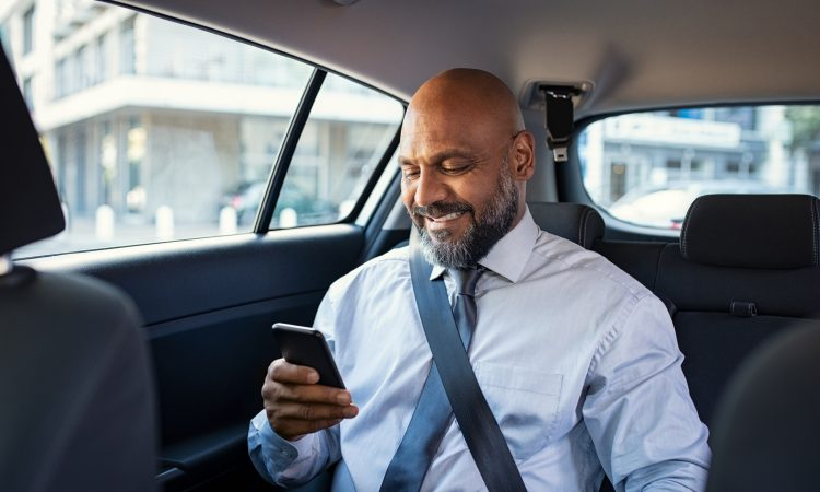 man reading on phone in back of car
