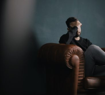 man sitting on couch with head in hand