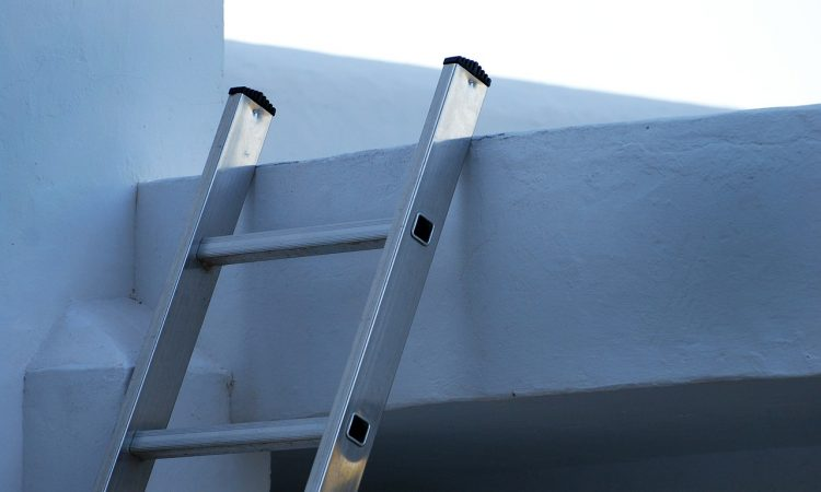 ladder propped up against white building