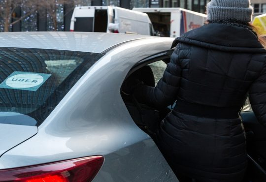A woman in a black coat is getting inside of a Uber car