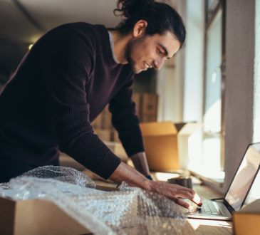 Young man working on laptop with parcel on the side.