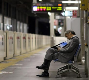 japanese buisnessman asleep on bench at train station