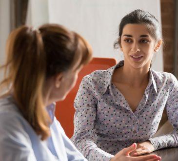 two women speaking in office
