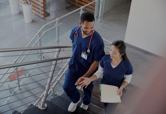 male and female nurse walking up hospital stairs