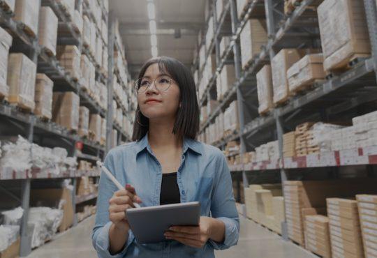 women in warehouse holding clipboard