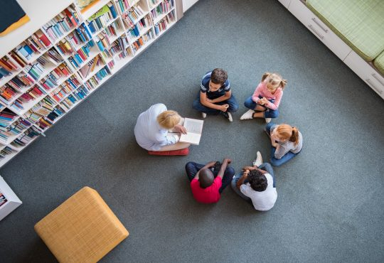 Teacher reading fairy tales to children sitting in a circle at library.
