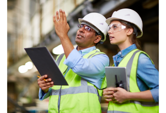 man and woman wearing hard hats and safety vests