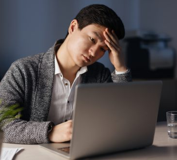 Tired businesman looking at laptop display in office