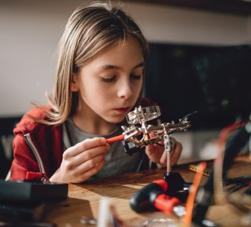 Girl wearing red hoodie looking circuit board throughout magnifying glass at home and building a robot