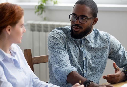 man and woman sitting and talking in office