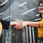 two people shaking hands in office