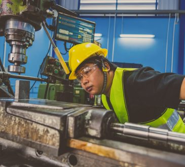 machinist in safety suit operating the professional lathes in metalworking factory