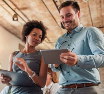 man and woman talking together in office looking at ipads