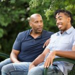 dad talking to son on park bench