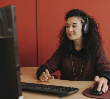 woman sitting at computer with headphones on