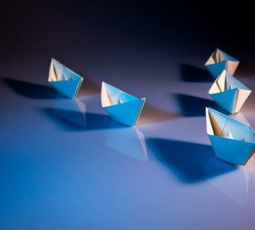 one paper boat leading other paper boats