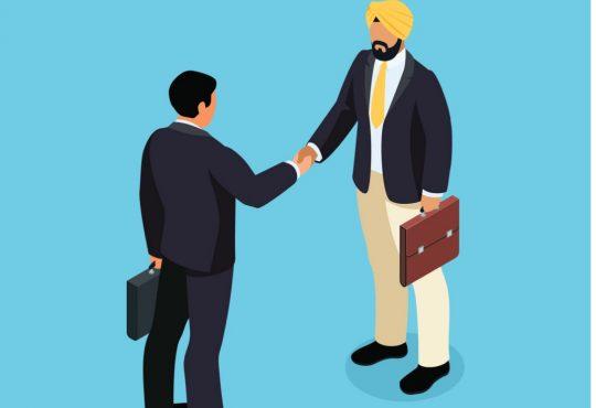 businessman wearing turban shaking other man's hand
