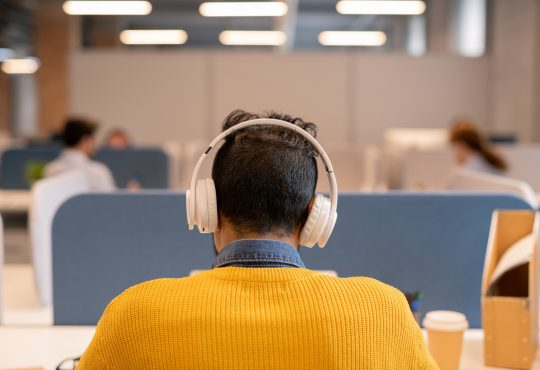 Rear view of busy brunette man in wireless headphones wearing bright sweater sitting at table in open space office a
