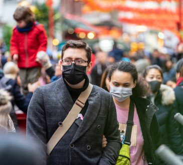 People walking in London wearing face masks.