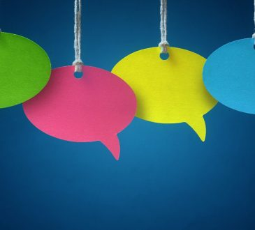 colourful speech bubbles hanging by threads on blue background