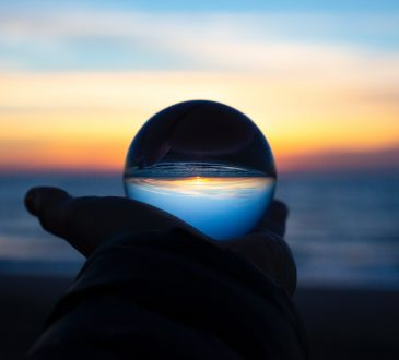 hand holding crystal ball in front of beach sunset
