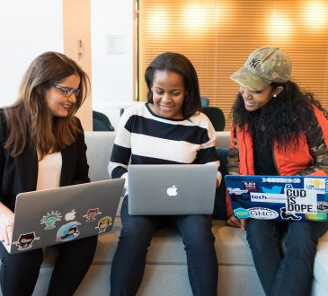 three women working on laptops together on couch