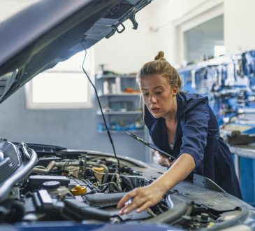 Female mechanic working on car
