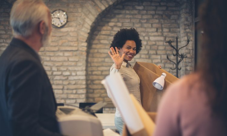 woman waving to colleagues leaving office