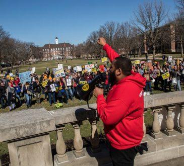 man shouting through megaphone at rally